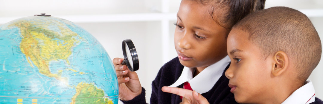 a boy and a girl using a magnifying glass and a globe